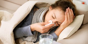 Sick woman on lounge covering nose with tissue