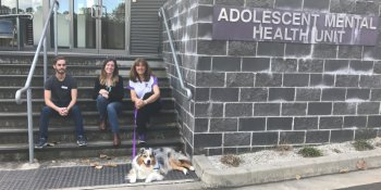 Staff sitting on front steps of building with dog