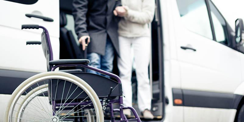 Image of people exiting a transport vehicle with a wheelchair waiting for them.