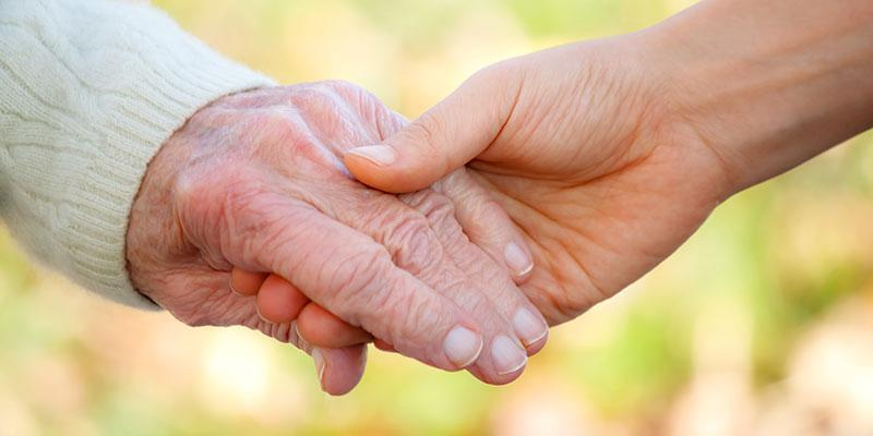 Image of a person holding an elderly patient's hand